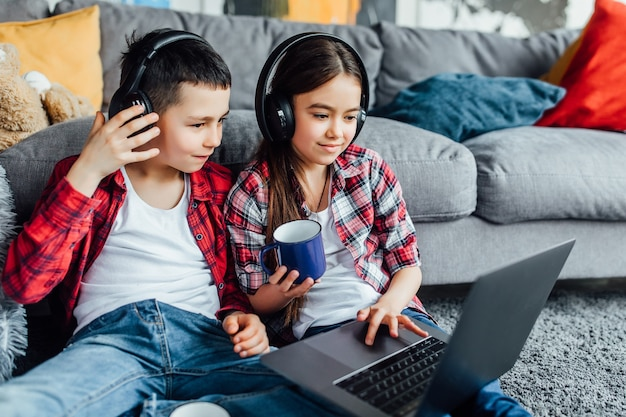 Porträt von bruder und schwester, die einen lustigen film mit kopfhörern ansehen, während sie einen laptop benutzen