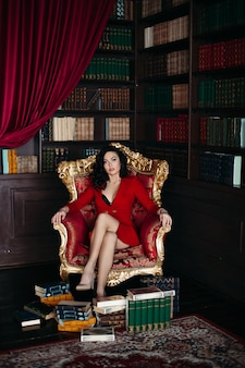 Porträt von brunette im roten kleid, das auf lehnsessel am bibliotheksinnenraum sitzt.