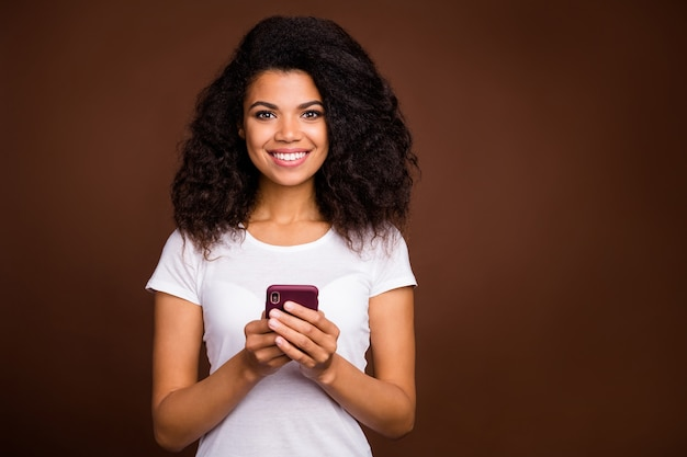 Porträt von charmanten positiven afroamerikanischen mädchen verwenden handy genießen bloggen sozialen netzwerk liebhaber tragen stilvolle kleidung.