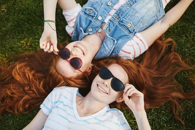Porträt von charmanten und sorglosen rothaarigen weiblichen geschwistern mit sommersprossen, die auf gras im park liegen und trendige sonnenbrille tragen, während sie lachen und lächeln, form der wolken besprechen.