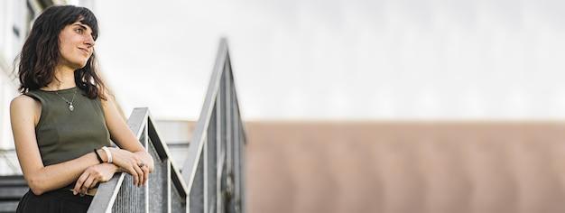 Porträt von daydreaming brunette girl stand auf städtischen treppen, bannerbild mit kopienraum