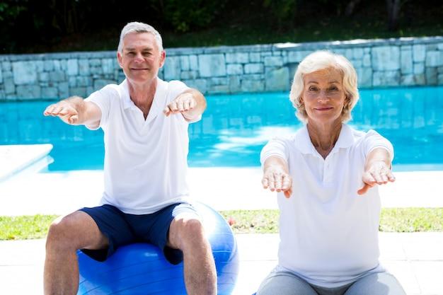 Porträt von den älteren paaren, die aerobic am poolside tun