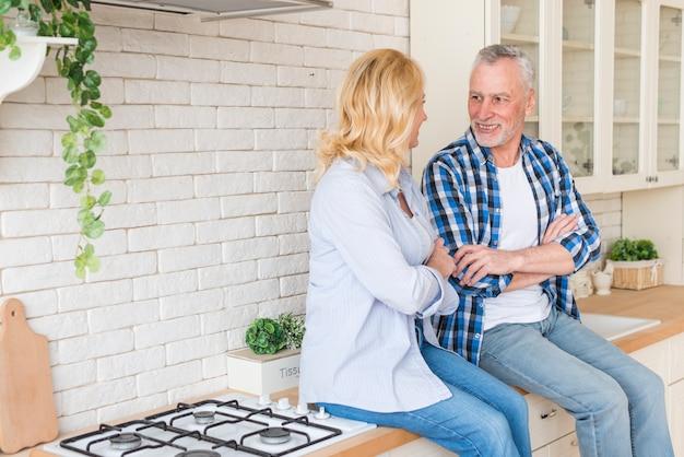 Porträt von den älteren paaren, die auf der küchentheke einander betrachtend sitzen