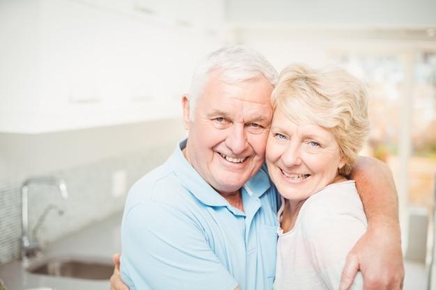 Porträt von den älteren paaren, die in der küche lächeln