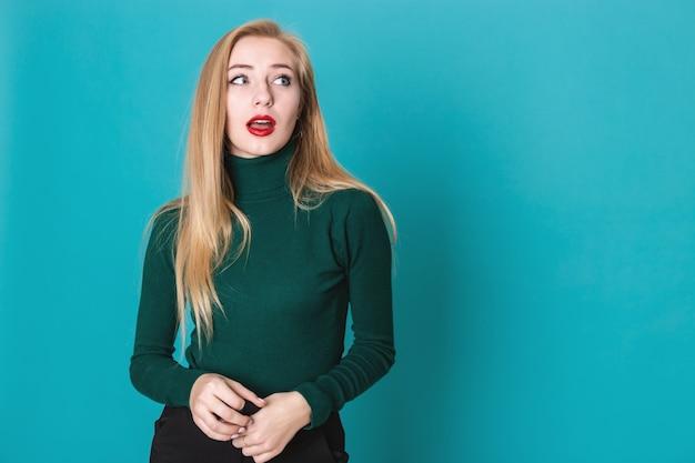 Porträt von den amased schönen blondinen, die gegen einen blauen hintergrund stehen