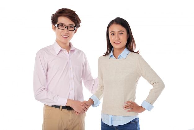 Porträt von den asiatischen jugendlichen, welche die handstellung rütteln