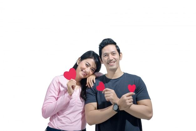 Porträt von den asiatischen paaren, die mit roten papierherzen stehen