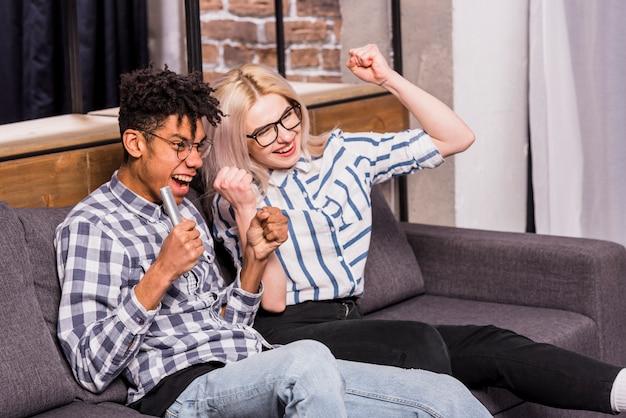 Porträt von den aufgeregten jugendpaaren, die auf dem sofa zusammenpreßt ihre faust sitzen