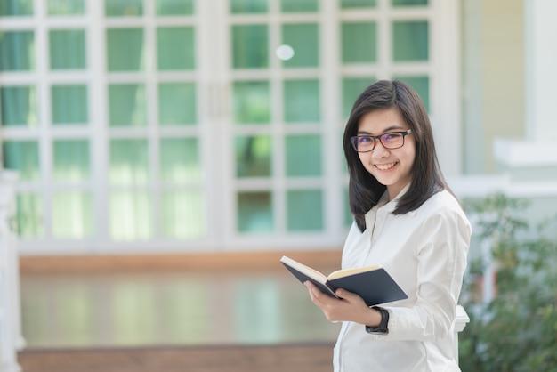 Porträt von den berufstätigen frauen, die anmerkungsbuch halten und glücklich, geschäftskonzept