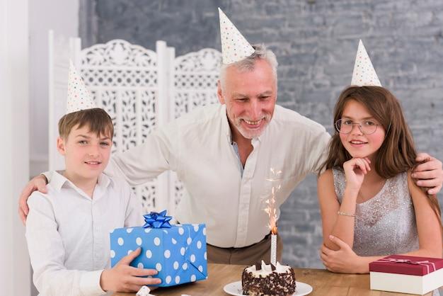 Porträt von den enkelkindern, die geburtstagsfeier ihres großvaters mit kuchen und geschenkboxen genießen