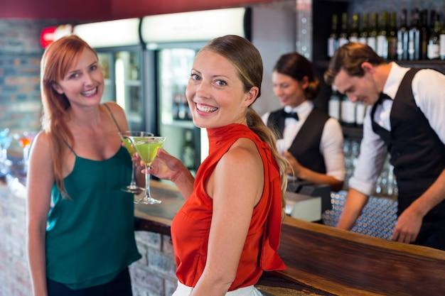 Porträt von den freunden, die ein cocktail vor barzähler halten