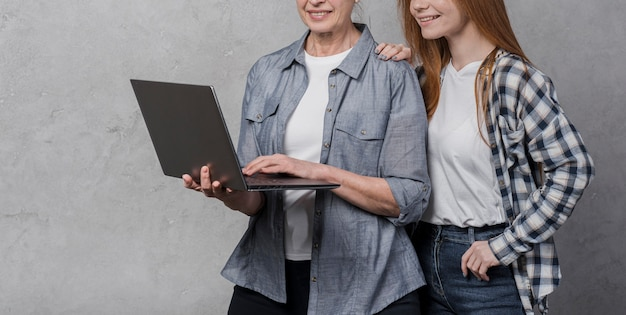 Porträt von den freundinnen, die einen laptop grasen