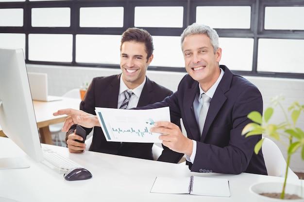 Porträt von den geschäftsleuten, die am computertisch arbeiten