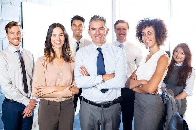 Porträt von den geschäftsleuten, die mit den armen stehen, kreuzte im büro