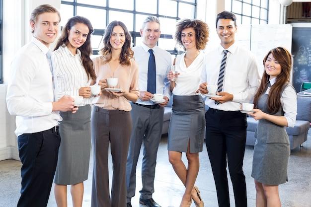 Porträt von den geschäftsleuten, die zusammen stehen und im büro während der pause lächeln