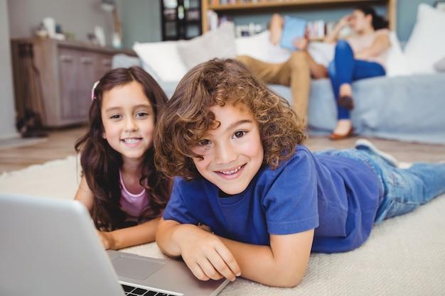 Porträt von den geschwistern, die durch laptop auf teppich liegen