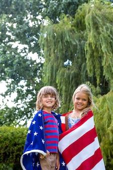 Porträt von den geschwistern, die in der amerikanischen flagge am hinterhof eingewickelt werden