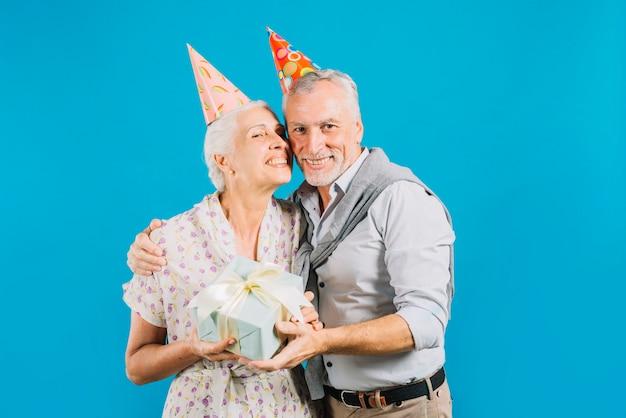 Porträt von den glücklichen älteren paaren, die geburtstagsgeschenk auf blauem hintergrund halten