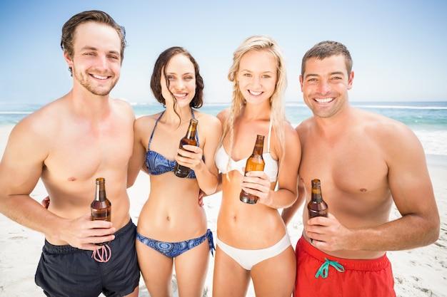 Porträt von den glücklichen freunden, die auf dem strand mit bierflaschen stehen