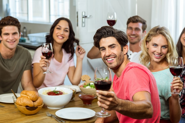 Porträt von den glücklichen freunden, die bei tisch weingläser halten
