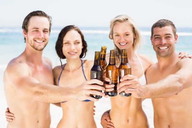 Porträt von den glücklichen freunden, die bierflaschen auf dem strand rösten