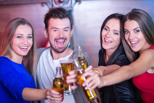 Porträt von den glücklichen freunden, die gläser mit cocktails halten.