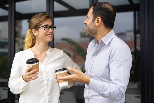 Porträt von den glücklichen geschäftskollegen, die an der kaffeepause sprechen