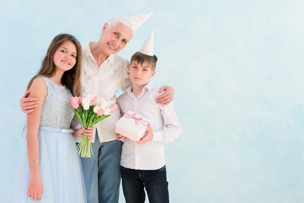 Porträt von den glücklichen kindern, die blumenblumenstrauß und geschenkbox mit ihrer großmutter halten