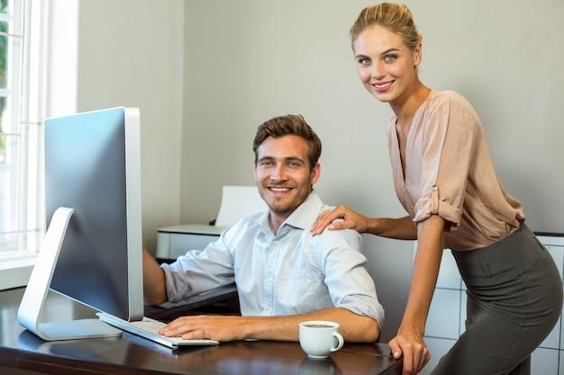 Porträt von den glücklichen kollegen, die im büro arbeiten