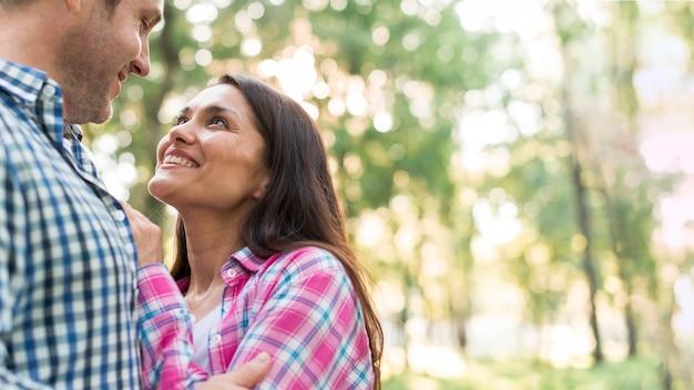 Porträt von den glücklichen netten liebhabern, die am park umfassen