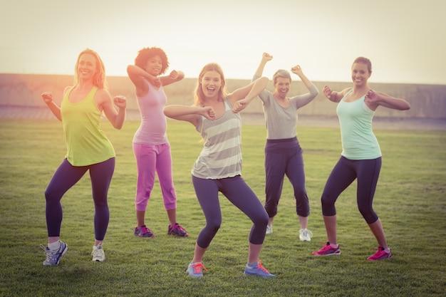 Porträt von den glücklichen sportlichen frauen, die während der eignungsklasse im parkland tanzen