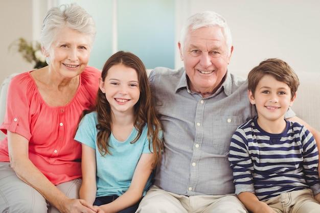 Porträt von den großeltern und von enkelkindern, die zusammen auf sofa im wohnzimmer sitzen
