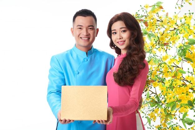 Porträt von den jungen asiatischen paaren, die eine geschenkbox zusammenhalten