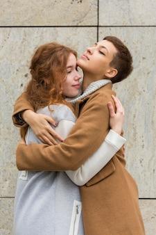 Porträt von den jungen frauen, die sich umarmen