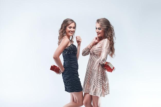Porträt von den jungen freundinnen, die geschenke hinter dem hinteren gehen halten, um sie auszutauschen.