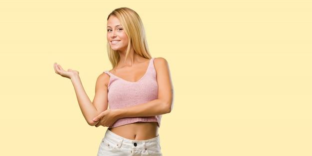 Porträt von den jungen hübschen blondinen, die etwas mit den händen halten, ein produkt zeigen, lächeln und nett