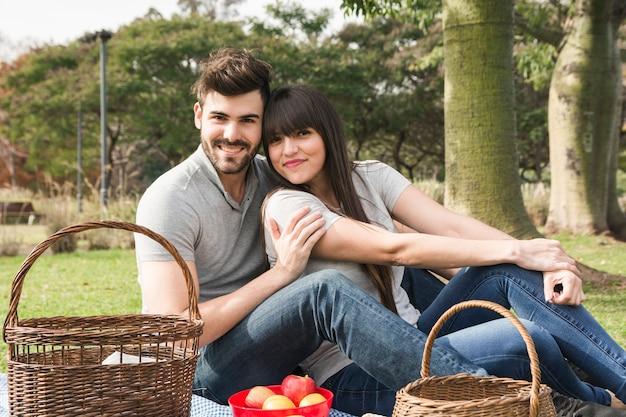 Porträt von den jungen lächelnden paaren, die im park mit früchten und picknickkorb sitzen