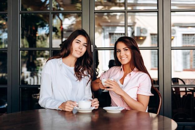Porträt von den jungen mädchen, die in der hand im restaurant mit schale sitzen