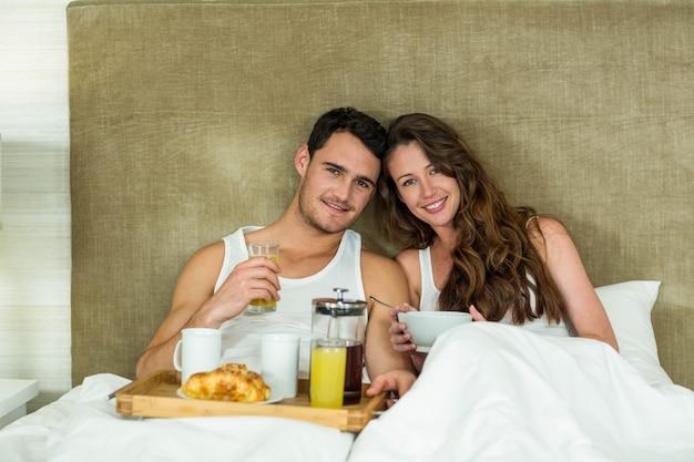 Porträt von den jungen paaren, die auf bett im schlafzimmer frühstücken