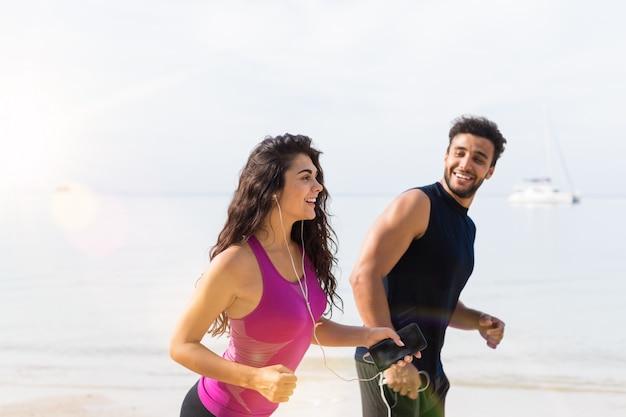Porträt von den jungen paaren, die auf dem strand-, glücklichen männlichen und weiblichen läufer laufen, die zusammen rütteln