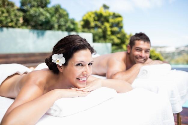 Porträt von den jungen paaren, die auf massagetabelle im badekurort lächeln und sich entspannen