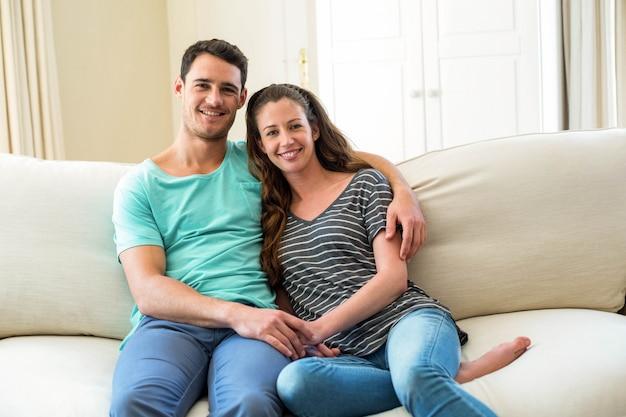 Porträt von den jungen paaren, die auf sofa im wohnzimmer sitzen