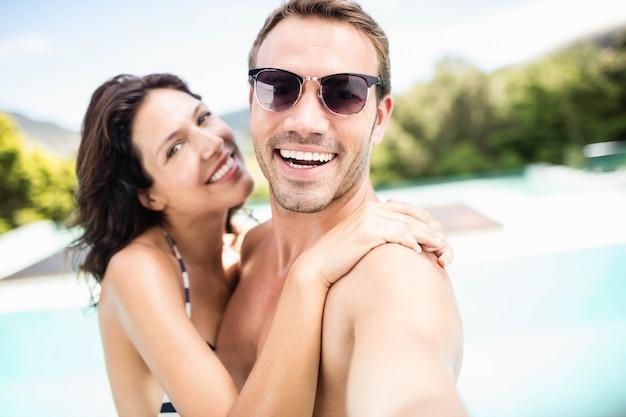 Porträt von den jungen paaren, die nahe pool an einem sonnigen tag lächeln