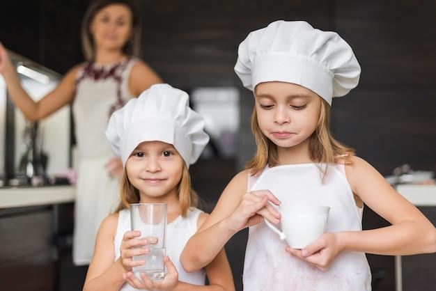 Porträt von den kleinen mädchen, die den chefhut halten, der glas und cup hält