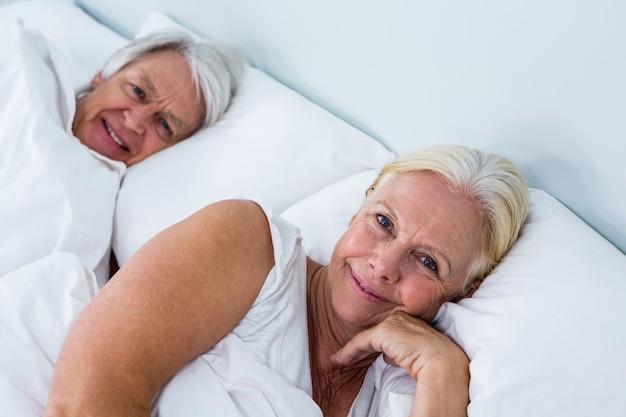 Porträt von den lächelnden älteren paaren, die auf bett schlafen