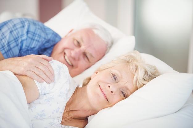 Porträt von den lächelnden älteren paaren, die auf bett sich entspannen