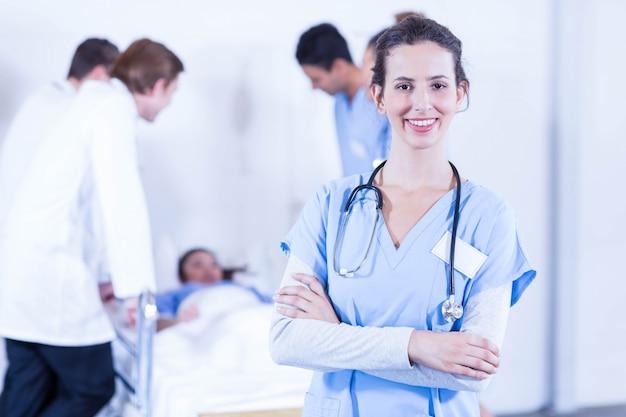 Porträt von den lächelnden ärztinnen und von anderem doktor, die hinten einen patienten überprüfen