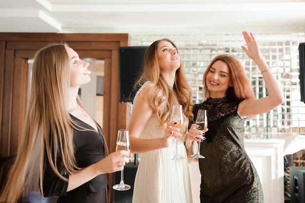 Porträt von den lächelnden freunden, die glas champagner halten