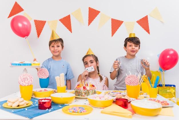 Porträt von den lächelnden freunden, die smileykarte halten; ballon und konfetti mit essen auf dem tisch