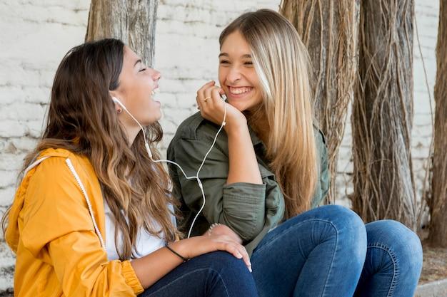 Porträt von den lächelnden freundinnen, die musik teilen